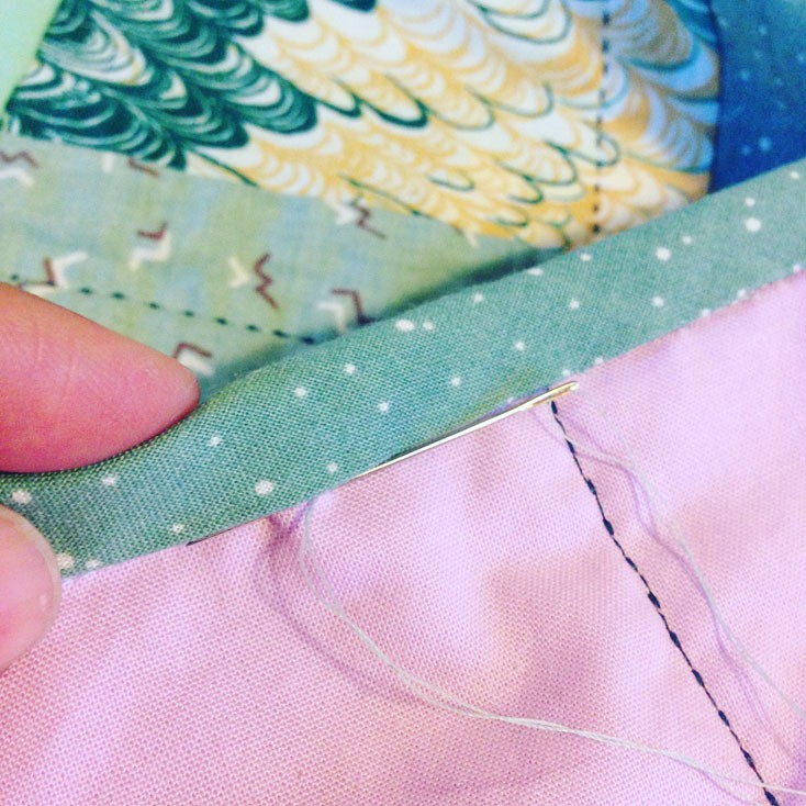 hand sewing bias tape to second side of quilt.
